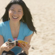 Asian woman laughing with magazine at beach — Stock Photo #13222910