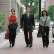 Business team walking down urban street — Stock Photo