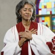 Stock Photo: AfricAmericfemale Reverend with hands on heart