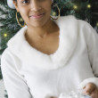 African woman holding gift in front of Christmas tree — Stockfoto