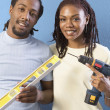 African couple with level and power drill — Stok fotoğraf