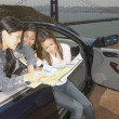 Stock Photo: Friends in convertible looking at map