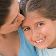 Portrait of mother kissing daughter — Stock Photo