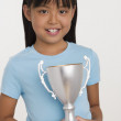 Stock Photo: Young Asigirl holding trophy and smiling
