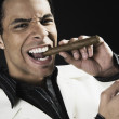 Stock Photo: Mixed Race mlighting cigar