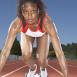Female track runner preparing to race - Stock Photo