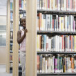 Stock Photo: Girl standing in library