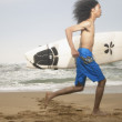 Young man running along beach with surfboard — Stock Photo #13223076