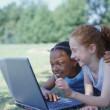 Two girls lying in park with laptop — Stock Photo