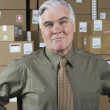Businessman standing in warehouse — Stockfoto