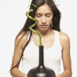 Young woman holding a plant in a vase - Foto de Stock