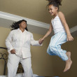 Stock Photo: Africmother and daughter jumping on bed
