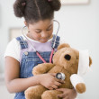 African American girl holding stethoscope on teddy bear — Stok fotoğraf