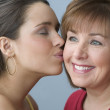 Teenage girl kissing her mother on the cheek — Stock Photo