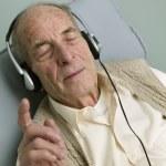 Elderly man listening to his headphones — Stock Photo