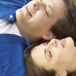 Couple laying in grass together - Stock Photo