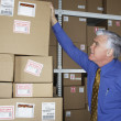 Businessman in warehouse looking at returned packages — Foto Stock
