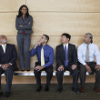 Businesswoman standing on a bench with co-workers looking at her — Stock Photo