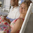 Middle-aged African American couple sitting in rocking chairs outdoors — Stock Photo