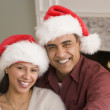 Hispanic couple wearing Santa Claus hats - Stock Photo