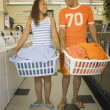 Couple carrying baskets of clothes in laundromat — Stock Photo #13223436