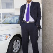 Hispanic car salesman next to new car — Stock Photo