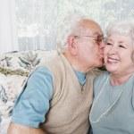Senior hombre besando a mujer senior en mejilla — Foto de Stock