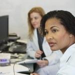 Two businesswomen at desks — Stock Photo