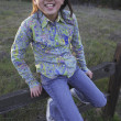Young Asian girl sitting on a fence - Foto Stock