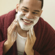 Stock Photo: African man applying shaving cream to face