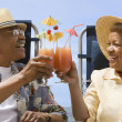 Senior African couple toasting with tropical cocktails — Stock Photo #13223573
