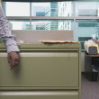 Stock Photo: Midsection businessmleaning on filing cabinet