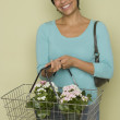 Hispanic woman carrying flowers in shopping basket — Stock Photo #13223594