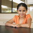 Burmese girl leaning on kitchen counter - Stock Photo