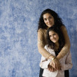 Hispanic mother and daughter hugging - Stock Photo