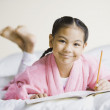 Pacific Islander girl writing in notebook - Stock Photo