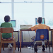 Rear view of two boys sitting in front of computers — Stock Photo