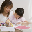 Asian mother watching daughter color — Stock Photo