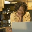Stock Photo: Young African woman in kitchen with laptop