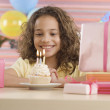 Young girl with cupcake and lit candles at birthday party — Stock Photo
