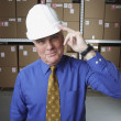 Businessman wearing hard hat and saluting in warehouse — Stockfoto