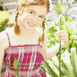 Stock Photo: Girl holding flower in sunlit garden