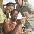 Foto Stock: Multi-ethnic friends drinking at restaurant