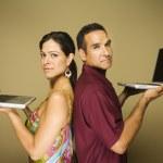 Hispanic couple standing back to back holding laptops — Stock Photo #13223770