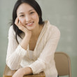Asiwomsitting at school desk — Stock Photo #13223799