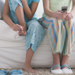 Girls painting toenails and holding cell phone — Stock Photo