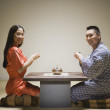Asicouple kneeling having tea — Stock Photo #13223832