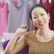 Asian woman smiling and holding shopping bag — Foto Stock