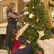 Hispanic family decorating Christmas tree — Stock Photo #13223945