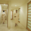Men in robes walking in a spa hallway - Stockfoto